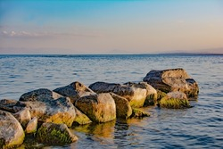 Stone path to the sea. Beautiful seascape with large stones on the sea. Blue sea and a pile of stones