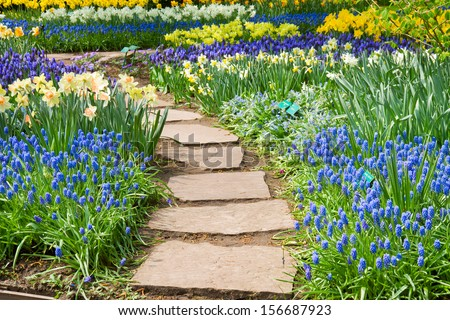 Stone path winding in spring flower garden
