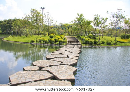 Stone Pathway in a Lush Green Park canal water.