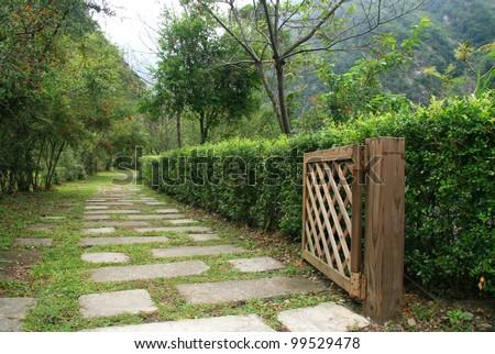 Stone pathway in garden with open wood door at Taroko National Park