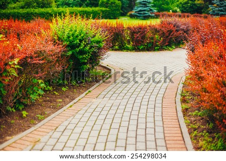 Stone Pathway Walkway Lane Path With Green Trees And Bushes In Garden. Beautiful Alley In Park. Beautiful Summer Park. Landscaping. Garden Design