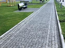 Stone pavement in perspective. Stone pavement texture. Granite cobblestoned pavement background. Abstract background of a cobblestone pavement