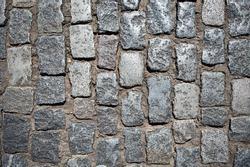 Stone pavement texture, granite cobblestoned pavement background, cobbled stone road regular shapes, abstract background of old cobblestone pavement close-up