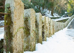 stone pillar on mountain forest path with snow path in winter, pathway with stone post in forest on mountain at asia japan