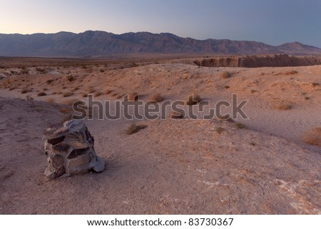Stone pole on desert with mountain range in the background