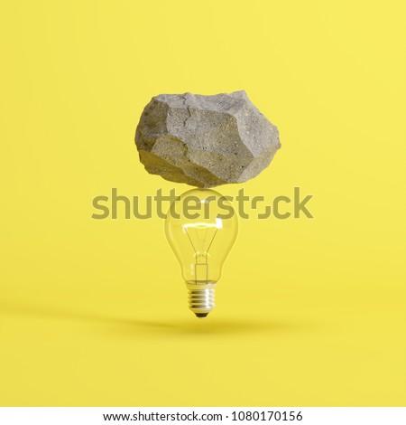 Stone put on  light bulb floating on yellow background. minimal creative idea concept.