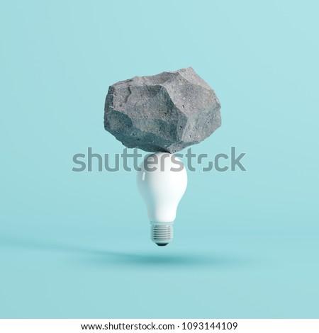 Stone put on White light bulb floating on blue background. minimal creative idea concept.