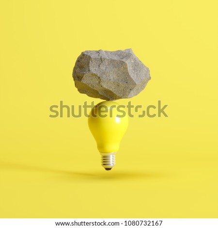 Stone put on yellow light bulb floating on yellow background. minimal creative idea concept. #1080732167