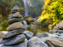 Stone pyramid near a tropical waterfall. The concept of harmony and balance. Stone Stacking or Stone Balancing.