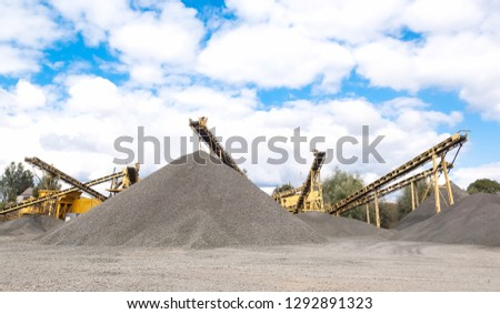 Stone quarry with conveyor belts and piles of stones. Quarrying of stones for construction works. #1292891323