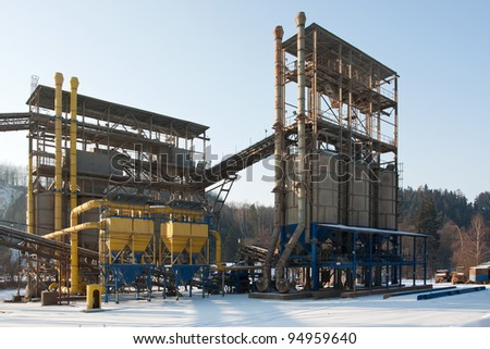 Stone quarry with silos and conveyor belts in winter