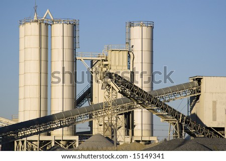 Stone quarry with silos, conveyor belts, and piles of stones.