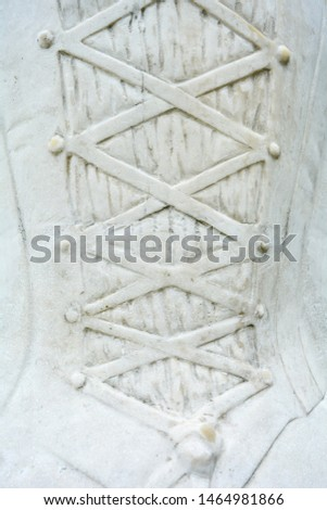 Stone relief with convex fragment of female costume in medieval old style with lacing with ribbon or wide cord. Marble carved surface with element of historical female dress #1464981866