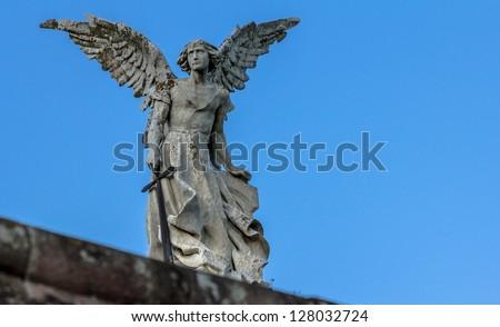 Stone sculpture of an archangel holding a sword.