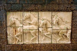 Stone sculpture of horse on brick wall with waterfall
