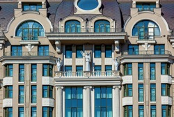 Stone sculptures of mythical creatures are placed on the facade of the building. A modern structure in classical style with big glass windows.
