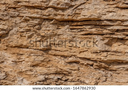 Stone shabby rocks and separated by large cracks and layers. Rough, rough gray stone or rocky mountain texture