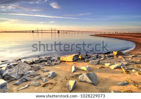 Stone silent sunrise on the Chesapeake Bay.  The sun paints a colorful morning sky over the Chesapeake Bay Bridge.  On the beach an assortment of stones lie peacefully, soaking in golden sunlight.