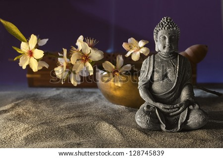 stone sitting buddha flowers and  Tibetan bowl