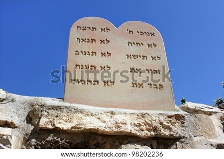 stone slab, in view of an open book, on which are engraved in Hebrew, nine biblical precepts