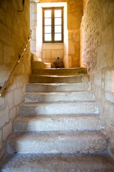 stone staircase leading to window in ancient stone stairwell