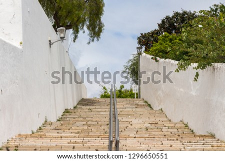 Stone staircase. Metal hand holders between staircases. White walls. #1296650551