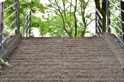 Stone stairs and metal railing in the park on a summer day. Summer.