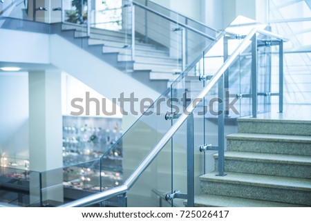 stone Stairs in modern interior. glass railing. Low Angle View Of Stairs Leading Towards modern building. Detail of stone steps of stairway in blue tone. mall inside business office building
