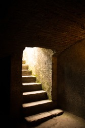Stone stairs leading into a dark room / cellar, light coming from above.