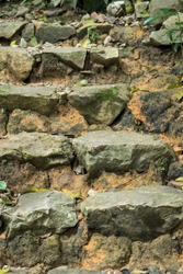 Stone Steps foot path made of rocks packed with mud close up selective focus in rain forest trail
