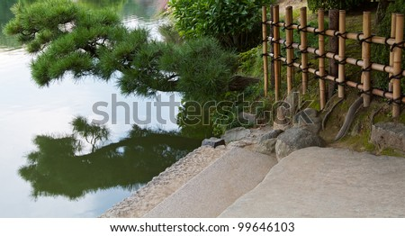 Stone steps lead down to water's edge, with pine bough overhanging and reflected in the calm water's surface. Traditional Japanese bamboo fence forms grid background. Horizontal landscape.