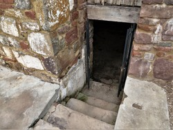 Stone steps leading into cellar of old stone  house