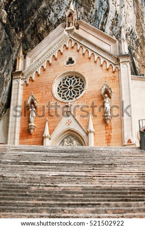 Stone steps of stairs to Ancient Madonna della Corona santuario facade under rocks in high mountains. Veneto region. Italy. Famous touristic landmark