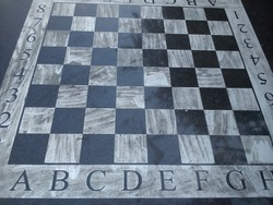 Stone table with a chessboard. Black and white chess fields. The letters A, B, C and D. Reflection of light on a polished surface. Monochrome squares