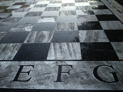 Stone table with a chessboard. Black and white chess fields. The letters E, F and G. Reflection of light on a polished surface. Monochrome squares.
