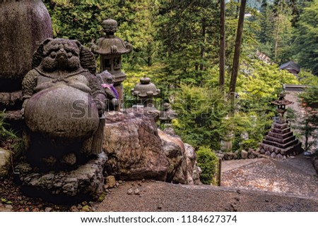Stone Tanuki Statue in Mysterious Buddhist Forest on Mountain Side, with Dense Tree Canopy, Stone Toro Lanterns, and Religious Stupas. Summer Day, No People (Kegonji, Gifu, Japan).