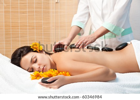 Stone therapy. Woman getting a hot stone massage at spa salon
