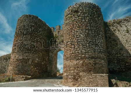 Stone thick towers in a sunny day beside the main entrance doorway on the outer wall of Evoramonte. A tiny fortified civil parish over hill where stands out its historic castle in Portugal. Stock foto ©