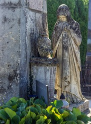 Stone tombstone in a cemetery in Croatia. Statue of Mother Mary. A symbol of faith, religion and god. All Saints' Day. Day of the Dead.