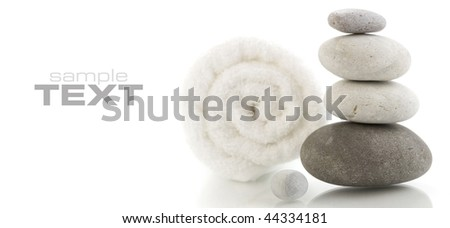 Stone tower and white towel with reflection on white background (with sample text)