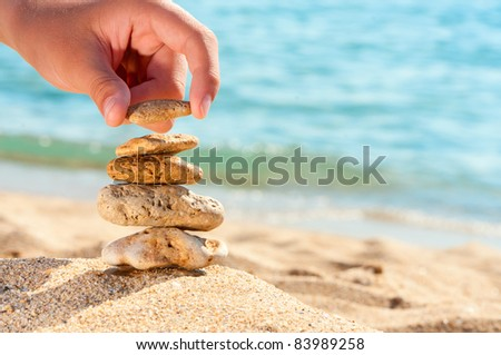 Stone tower on sand with hand against sea. Concept for rest, spa, relaxation, resorts.