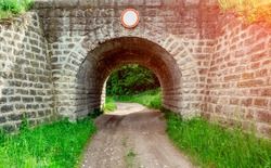 Stone tunnel for transport, road in the forest