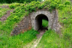 Stone tunnel overgrown with grass for pedestrians in the park
