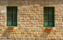 stone wall and green lattice windows of a Lebanese village house
