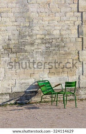 Stone wall and two green garden chairs in the morning sunlight in the Tuileries Garden, Paris, France (Vertical)
