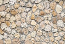 Stone wall background, beige cobblestones, abstract rocks texture, mineral pavement, light brick wallpaper, rough masonry. Grunge floor, boulders.