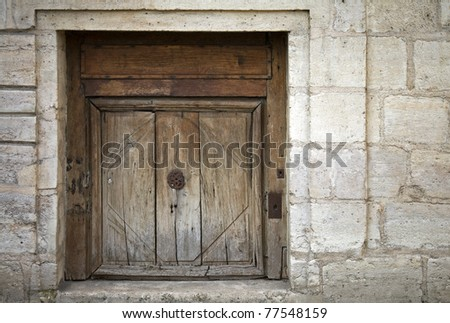 Stone wall of an ancient building with old weathered wooden gate