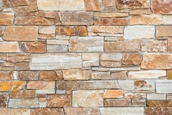 Stone wall of natural stones in different sizes; Rustic stone veneer in shades of brown and beige; Wall covering with natural stones