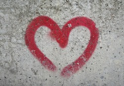 stone wall red heart . heart pattern on the stone wall . red outline of the heart on a gray background
