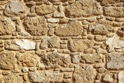 Stone wall texture background, exterior of ancient Greek house in Paphos Archaeological Park, Cyprus. Abstract pattern of old building wall close-up, rough yellow surface for backdrop or wallpaper.
